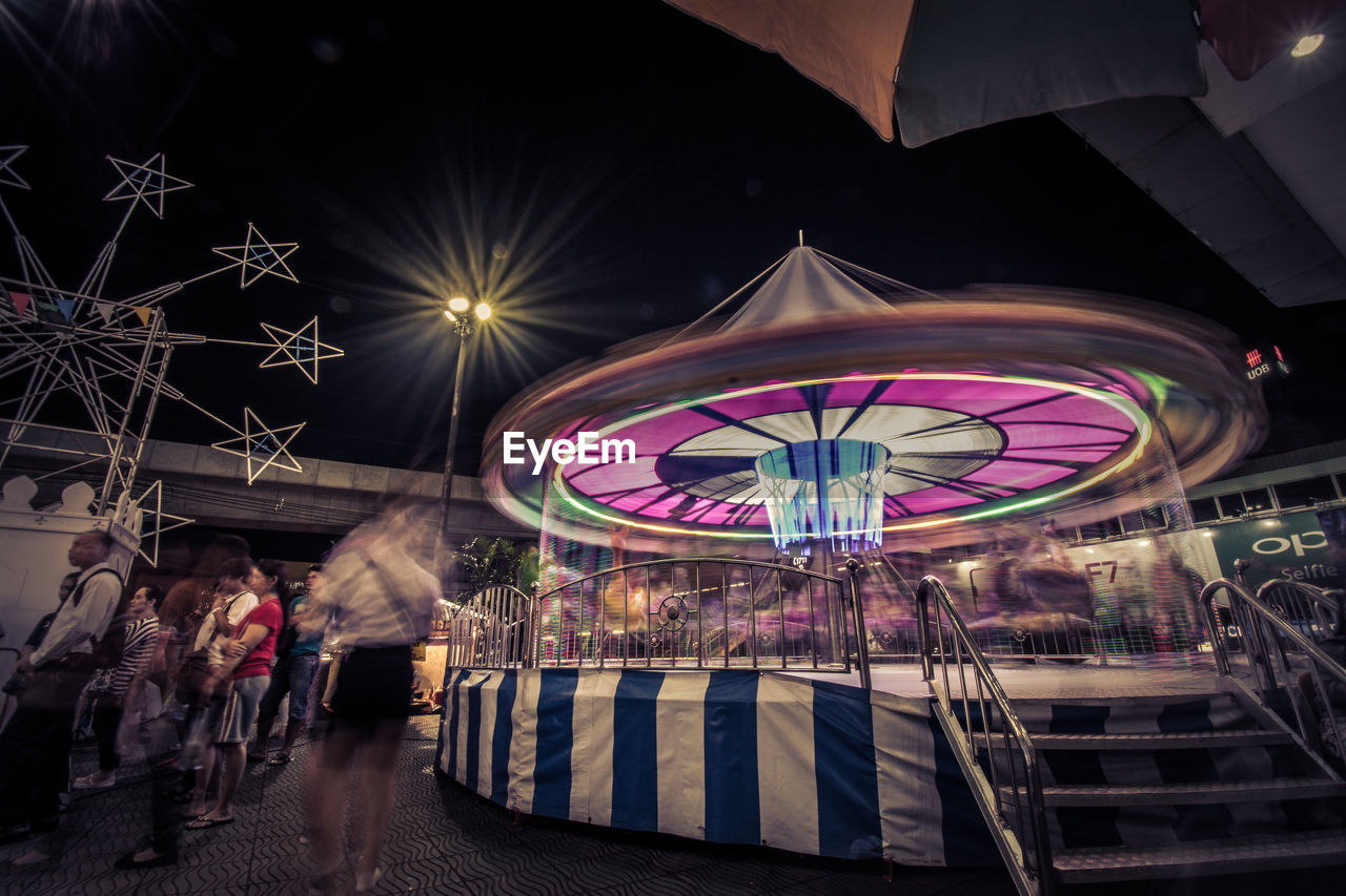 People At Illuminated Amusement Park During Night
