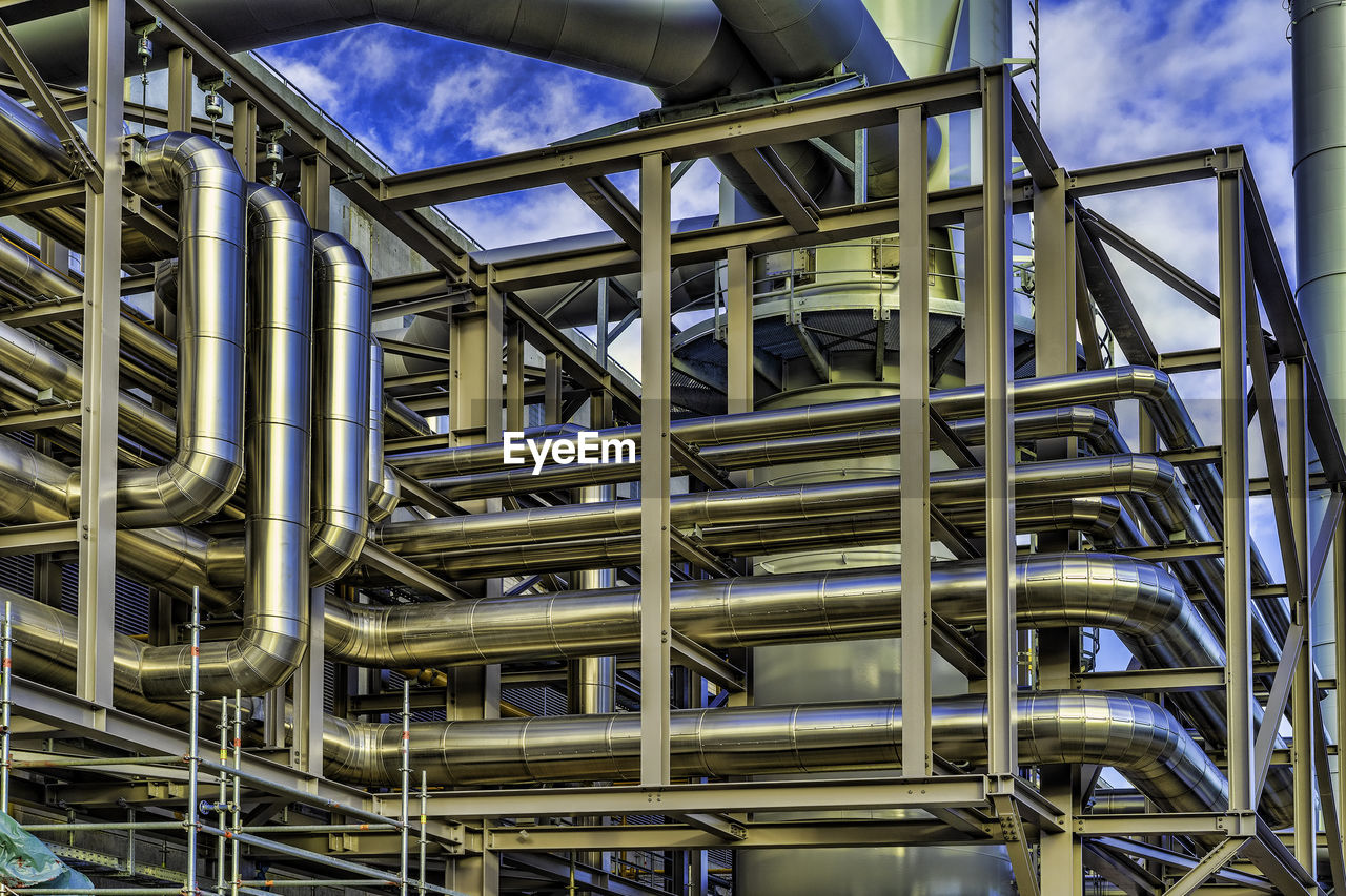metal, no people, built structure, architecture, day, industry, low angle view, pipe - tube, factory, cloud - sky, outdoors, sky, silver colored, blue, machinery, connection, business, modern, close-up, steel, industrial equipment