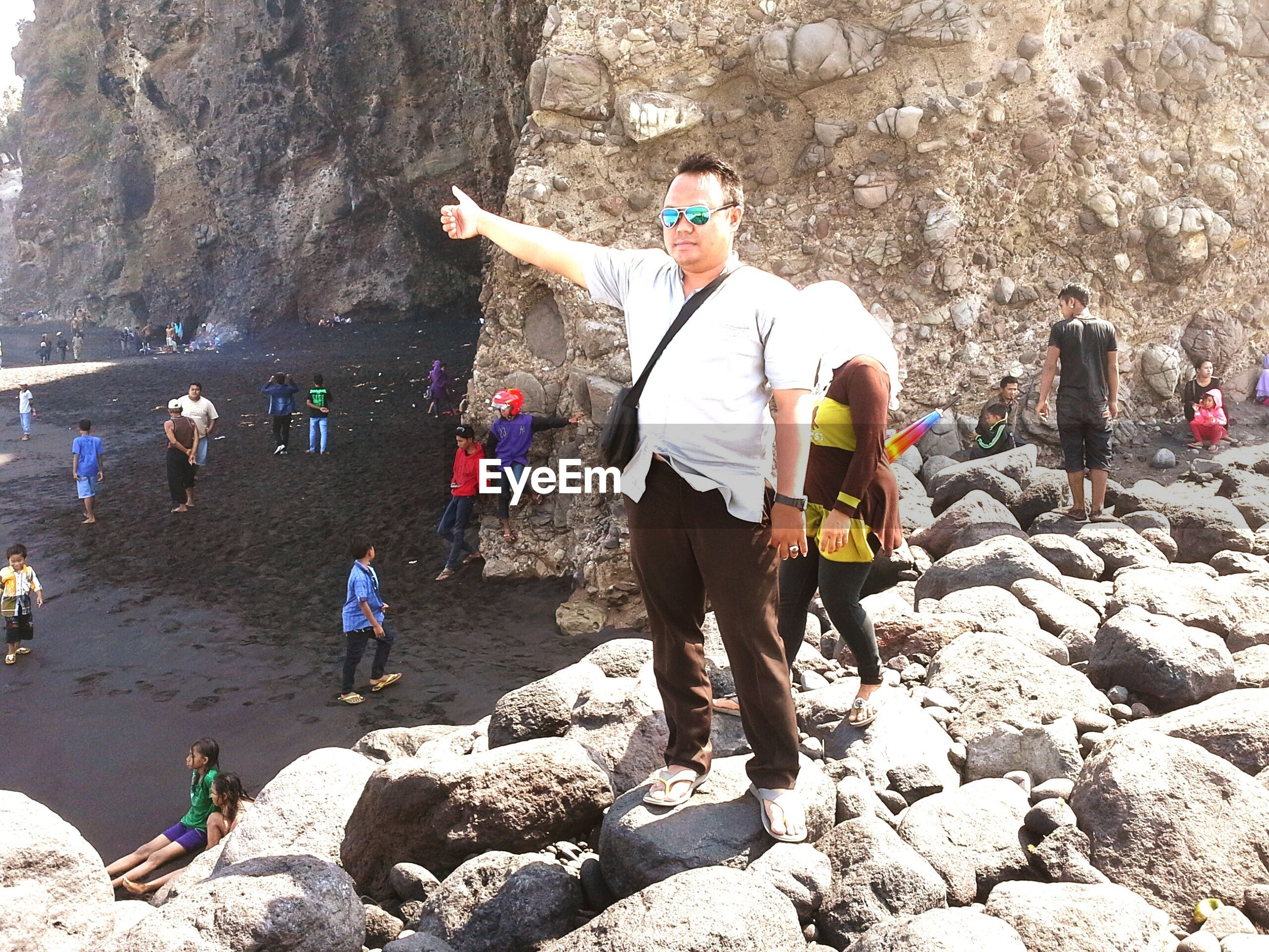rock - object, lifestyles, leisure activity, full length, men, rock formation, person, beach, water, vacations, shore, casual clothing, rock, tourist, sea, rear view, sand, sunlight, day