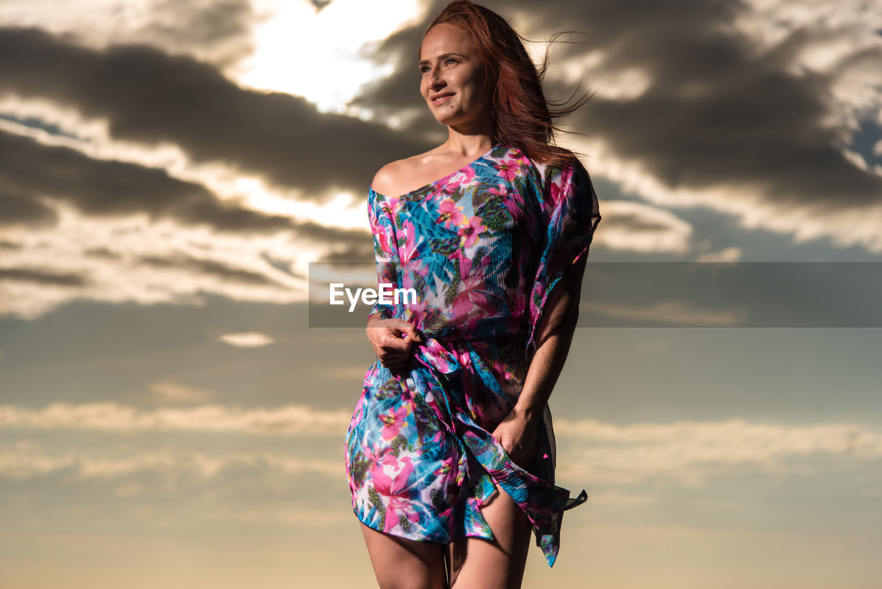 Low Angle View Of Beautiful Model Standing Against Sky