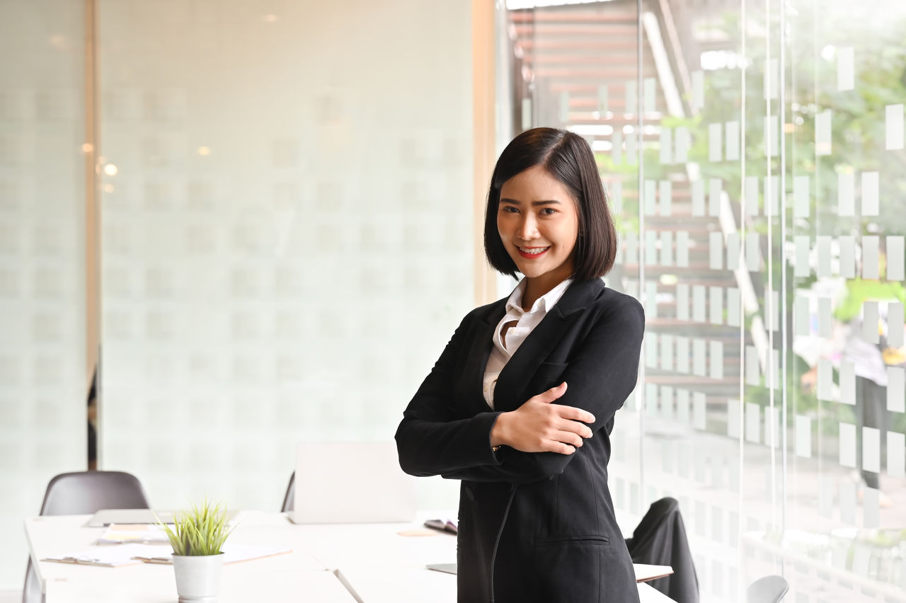 business person, looking at camera, business, office, portrait, businesswoman, one person, corporate business, smiling, adult, women, well-dressed, indoors, young adult, suit, three quarter length, young women, standing, businesswear, beautiful woman, hairstyle