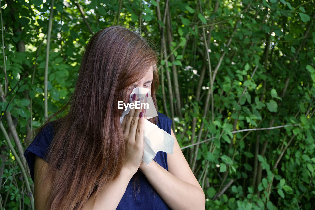 Sick woman wiping her nose against plants