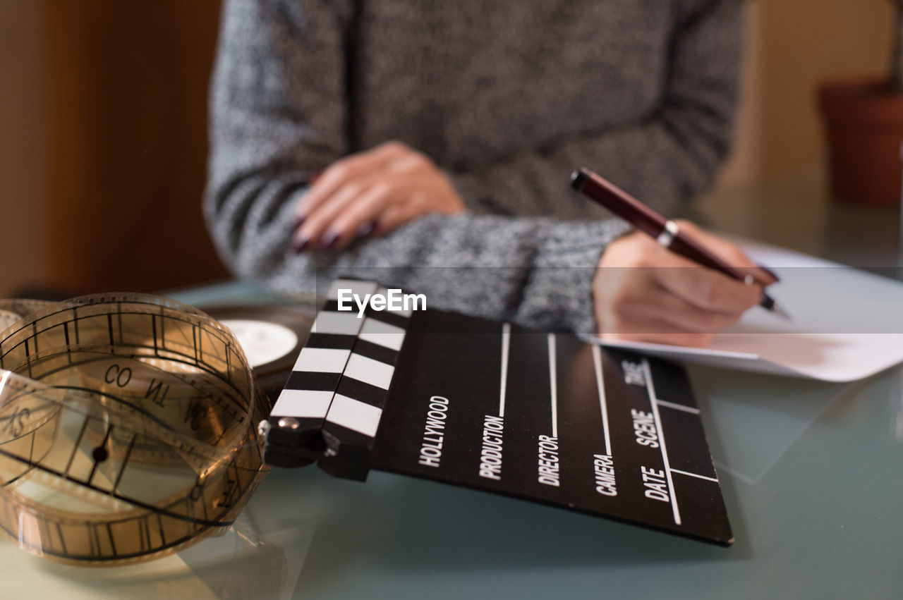 Midsection of woman writing on paper by film slate and reel at table