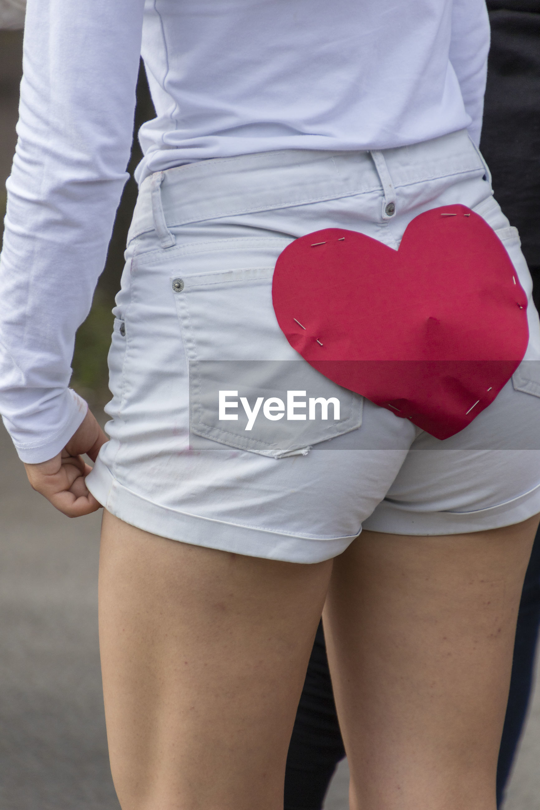 Midsection of young woman with heart shape paper on shorts