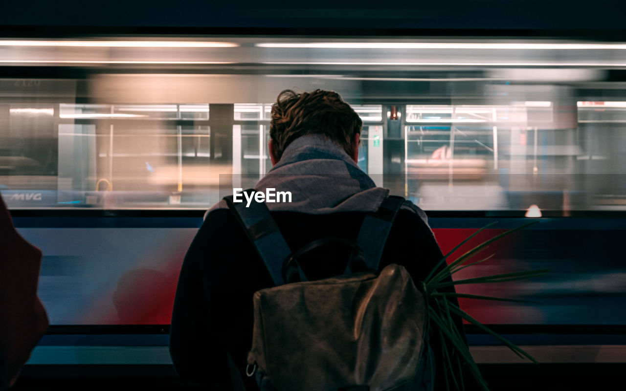 REAR VIEW OF MAN ON TRAIN AT ILLUMINATED RAILROAD STATION