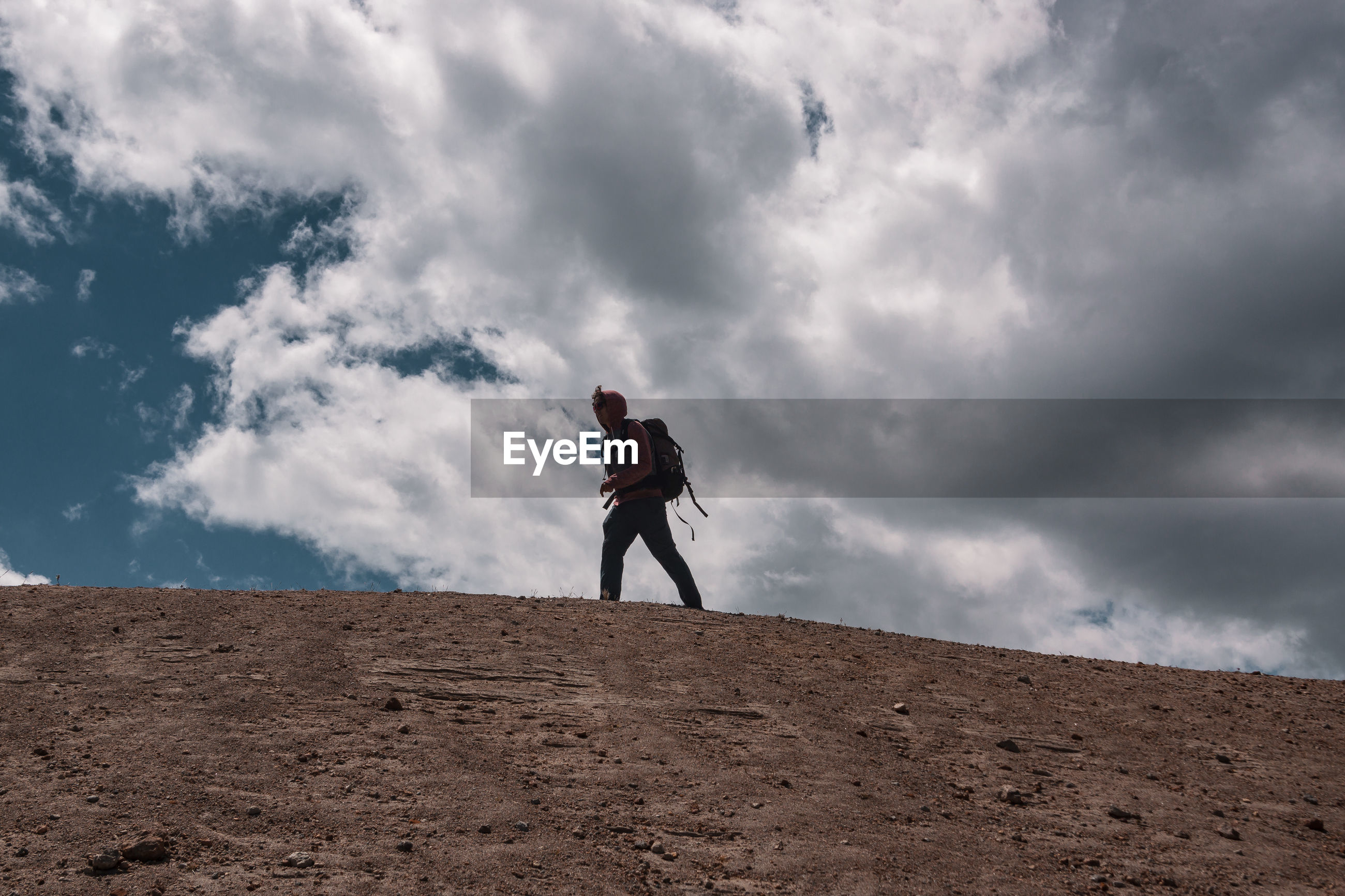 Low angle view of young man walking on mountain against cloudy sky