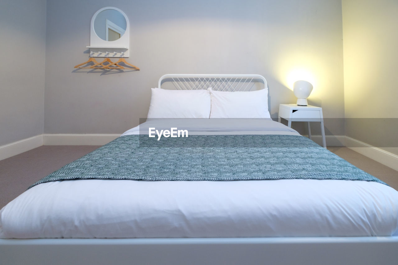 Arranged bed against wall in bedroom at home