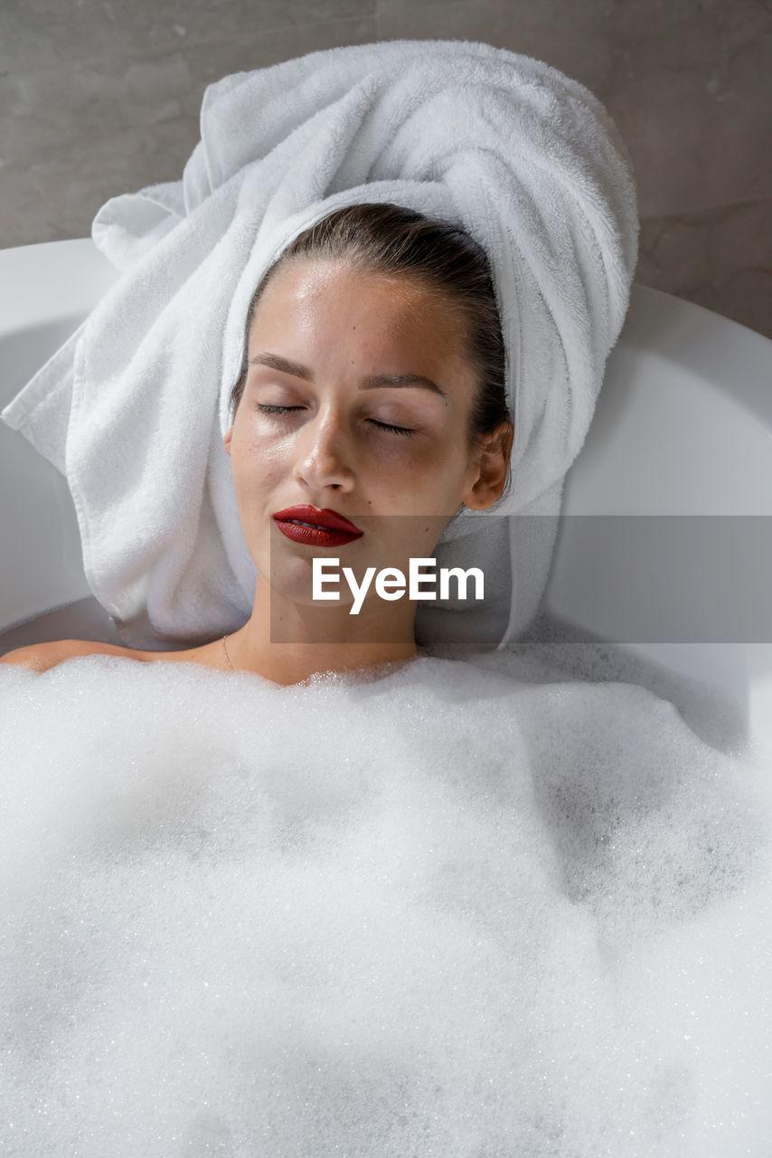Portrait of woman wearing red lipstick relaxing in bath