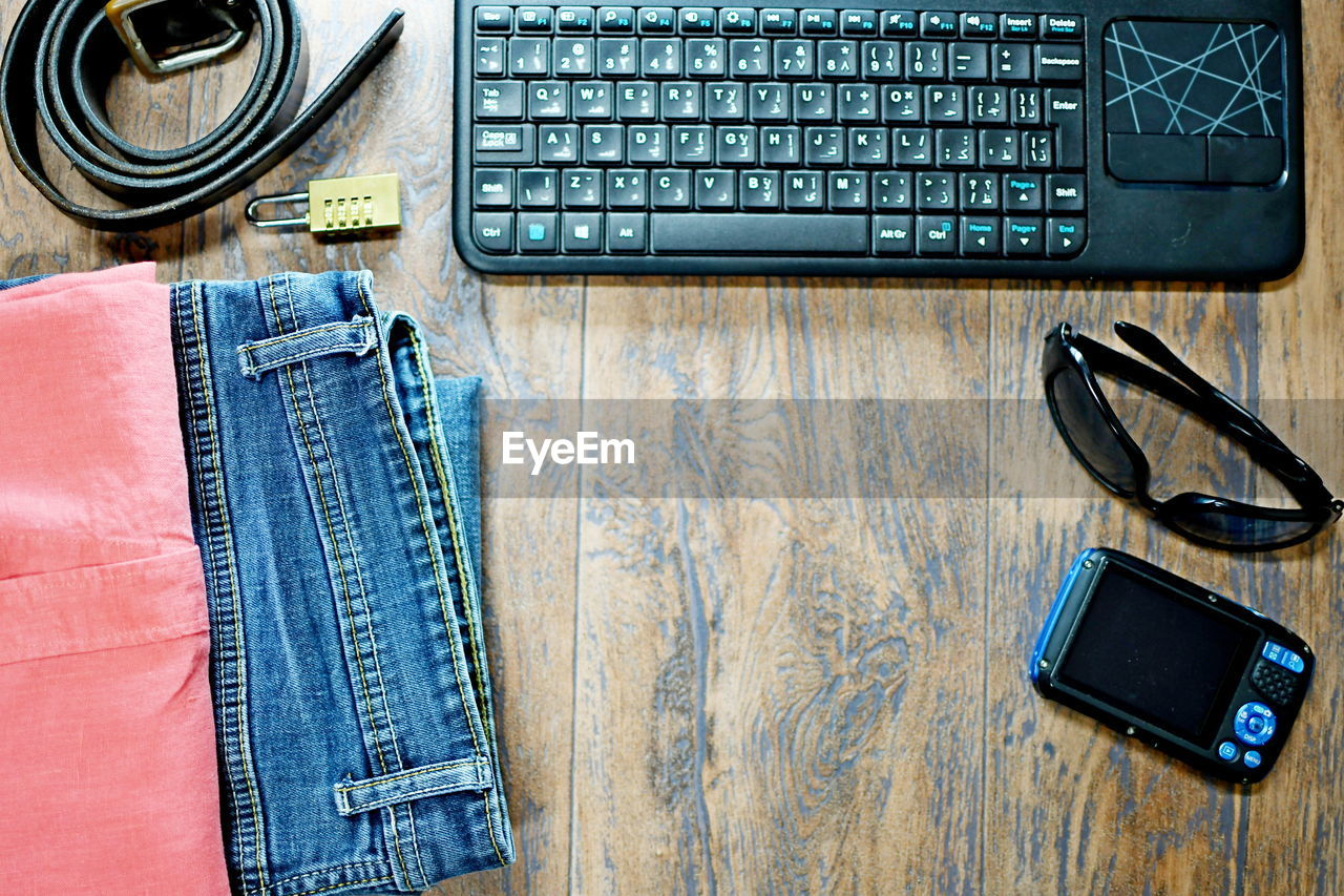 Directly above shot of technologies and personal accessories on wooden table