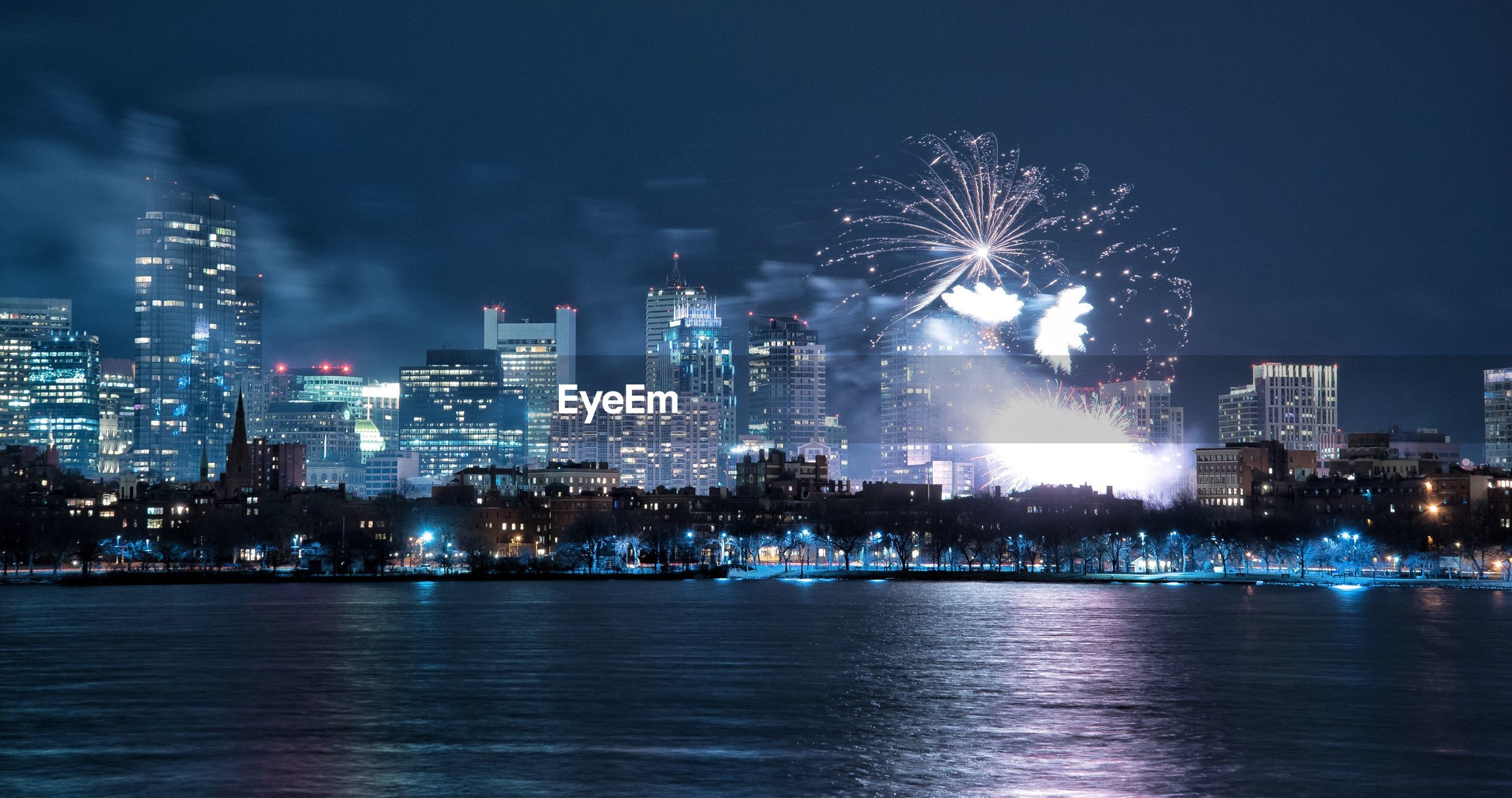 Firework display over city by river at night