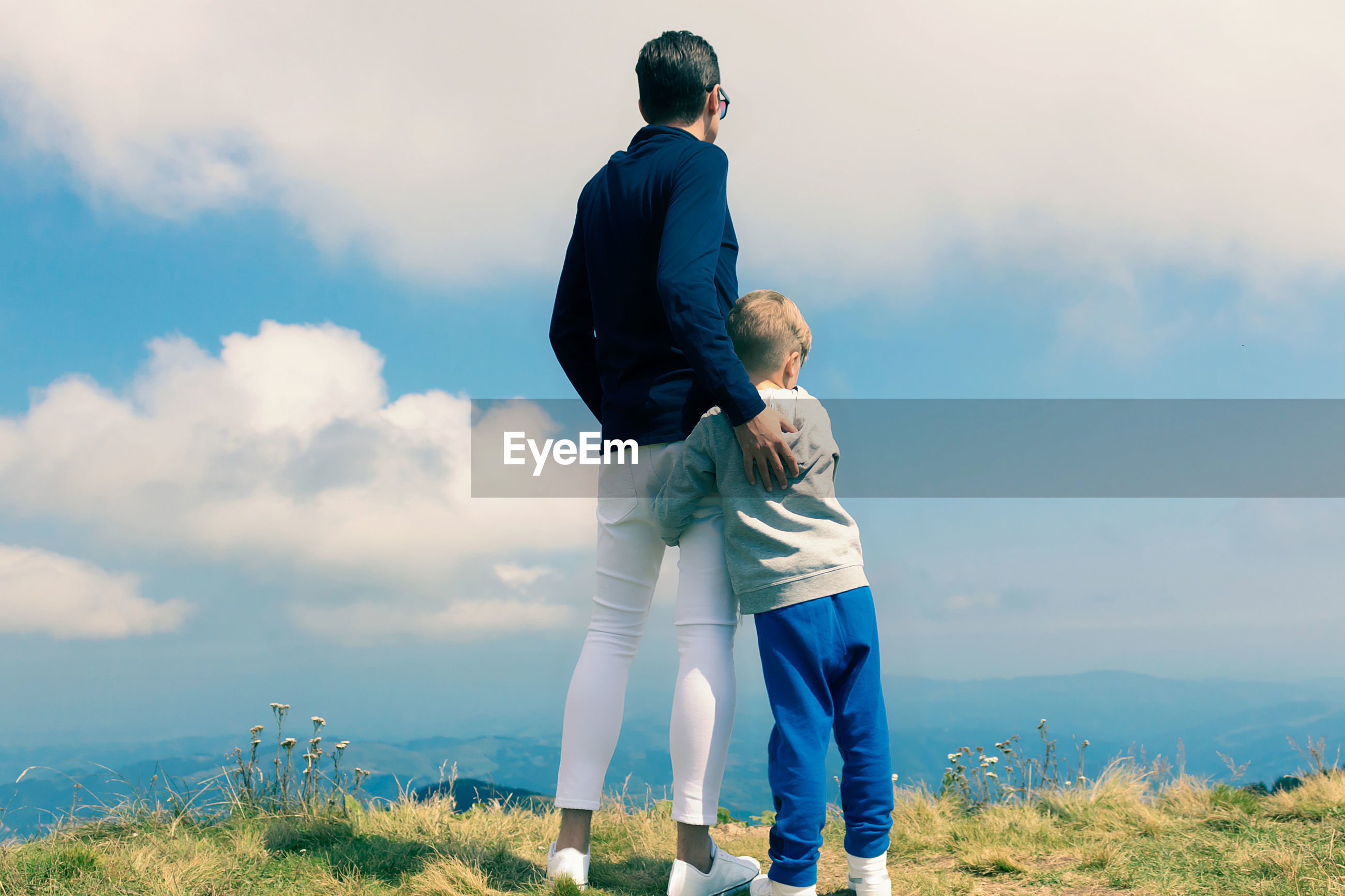 FULL LENGTH OF FATHER AND SON STANDING AGAINST SKY