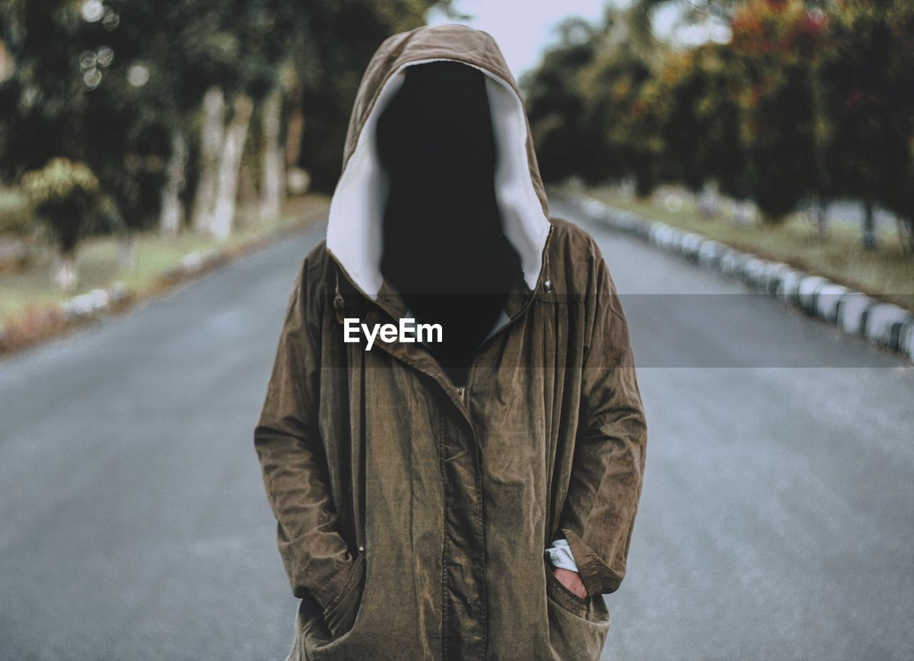 Digital composite image of invisible person wearing jacket on road