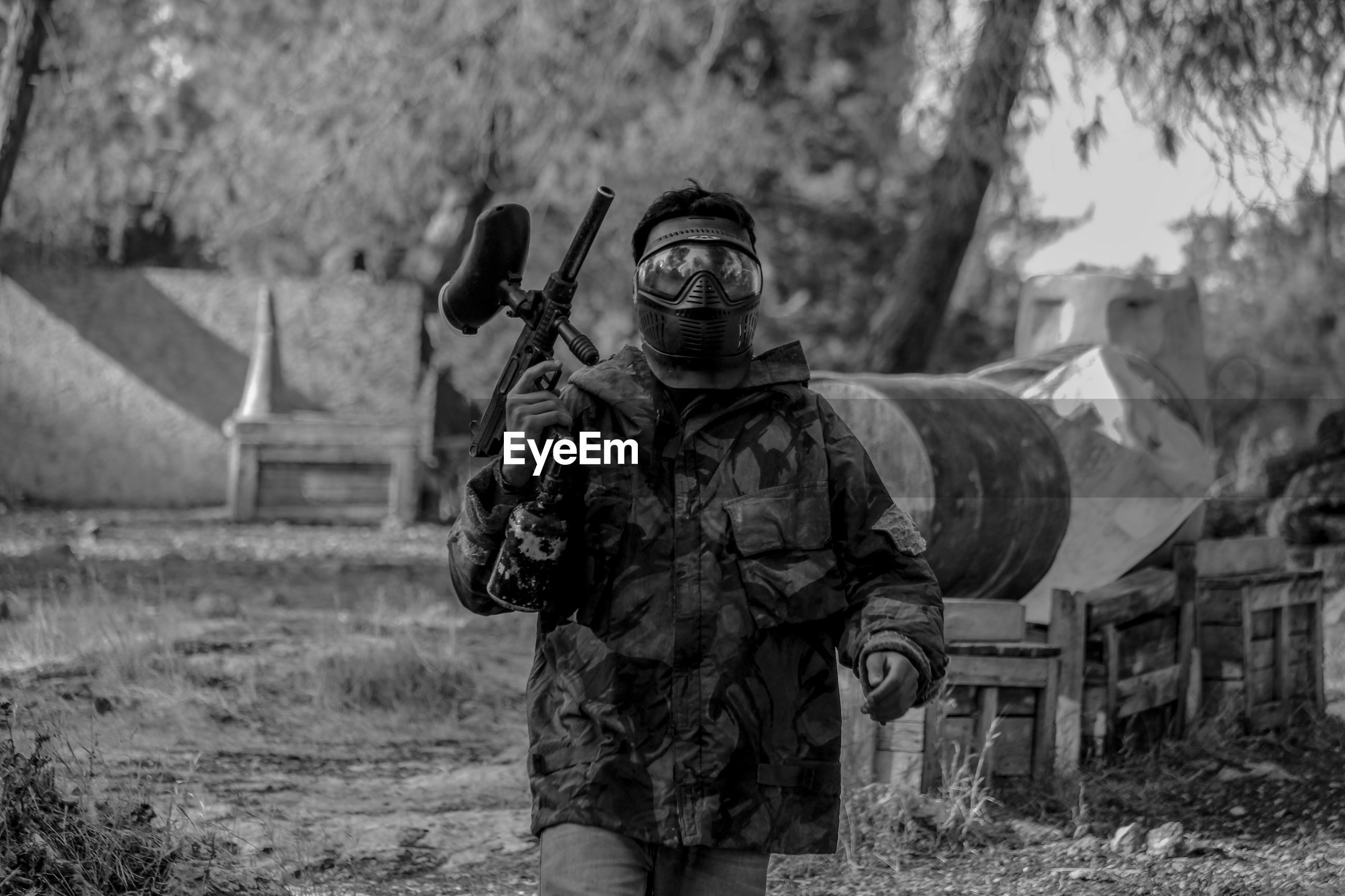 Man in camouflage clothing with paintball gun