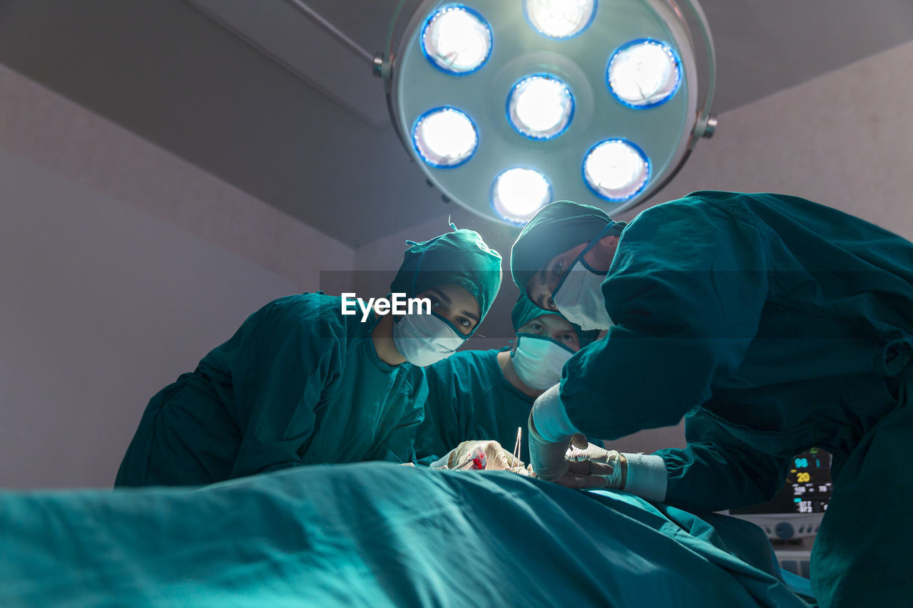 Group of doctor, concentrated doctor in a patient during a hysterectomy operation in a hospital.
