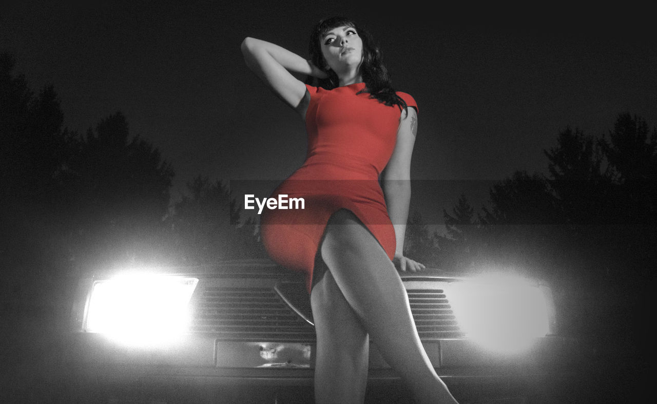 Woman in red dress sitting on car against sky