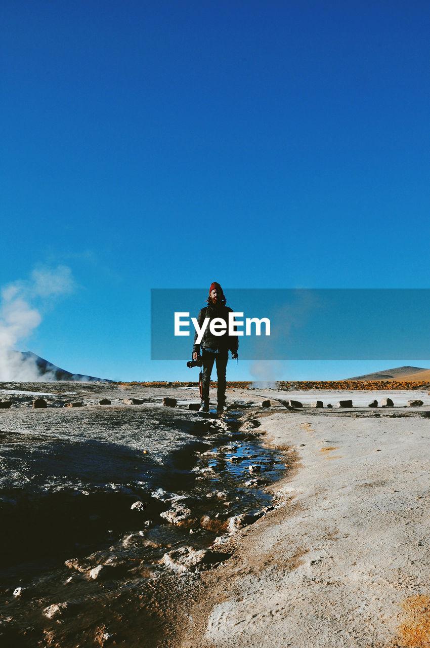 MAN STANDING IN DESERT AGAINST CLEAR BLUE SKY