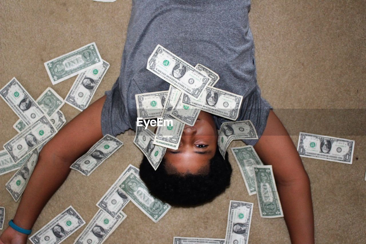 High Angle Portrait Of Boy Surrounded By Paper Currencies While Lying On Floor