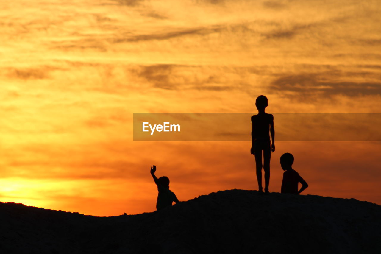 Silhouette Siblings Standing On Hill Against Cloudy Sky During Sunset