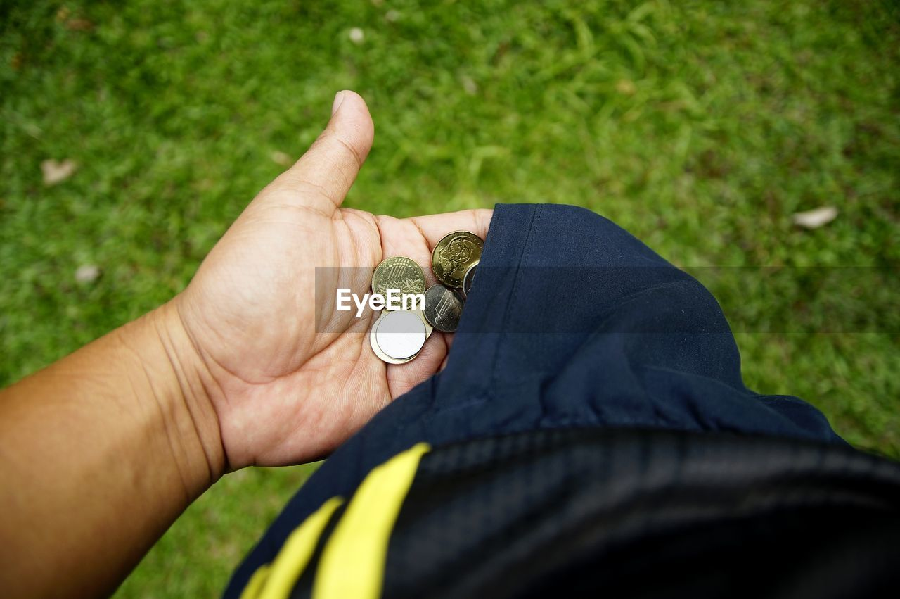 Midsection of man removing coins from pocket