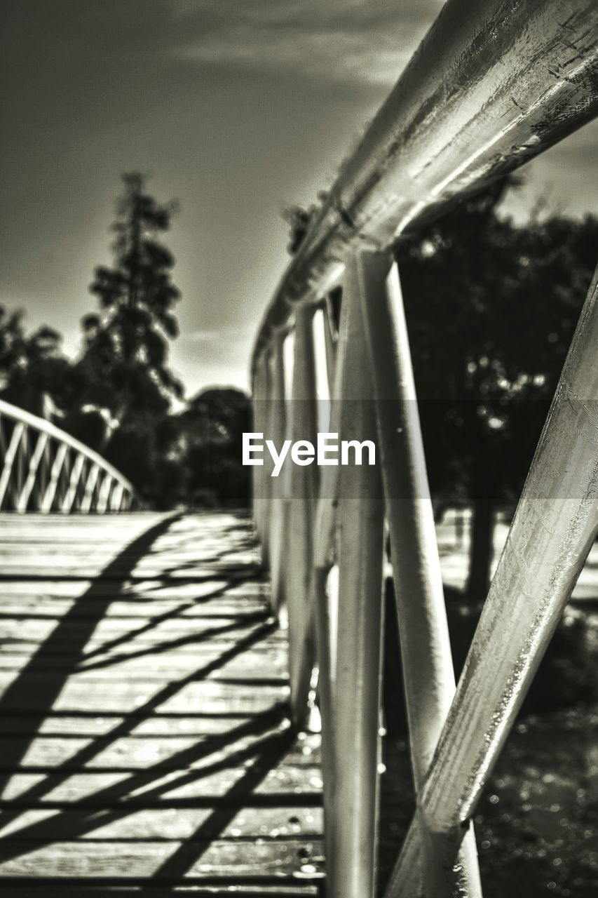 outdoors, day, railing, tree, focus on foreground, bridge - man made structure, sunlight, no people, sky, close-up, footbridge, nature