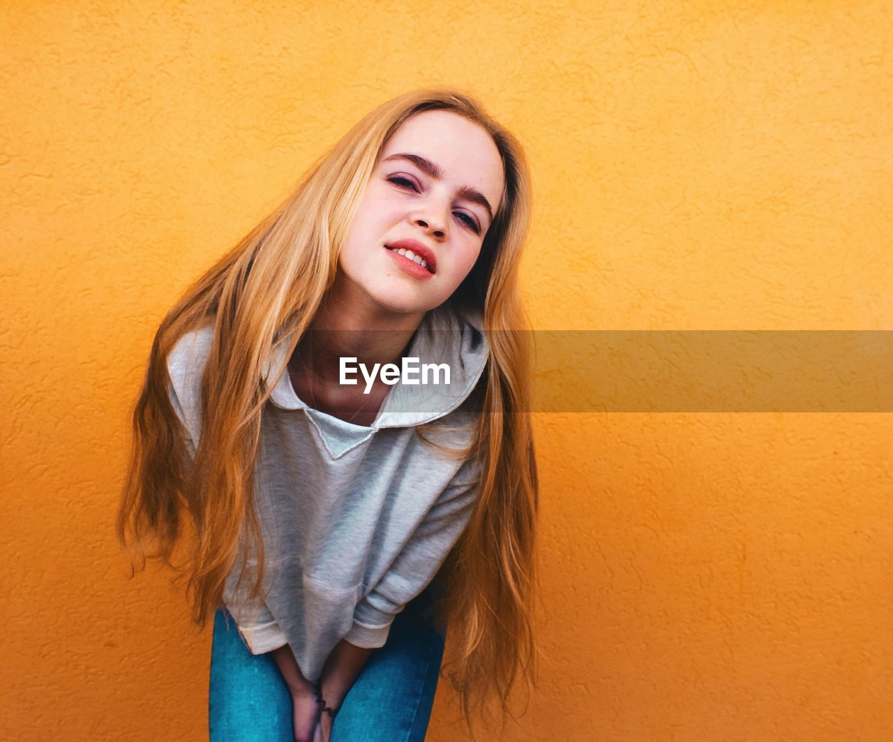 Portrait Of Young Woman Bending Against Orange Wall