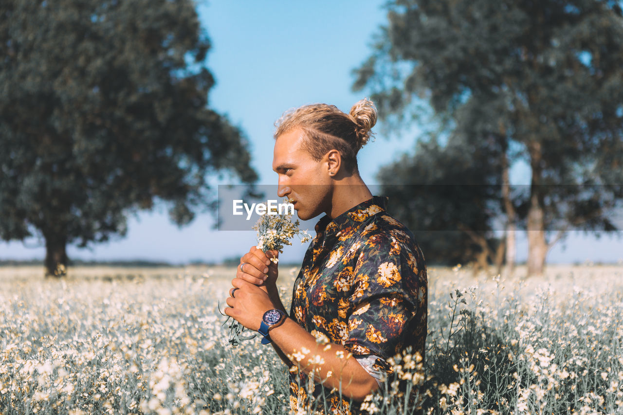 Man Smelling Flowers While Standing Against Trees