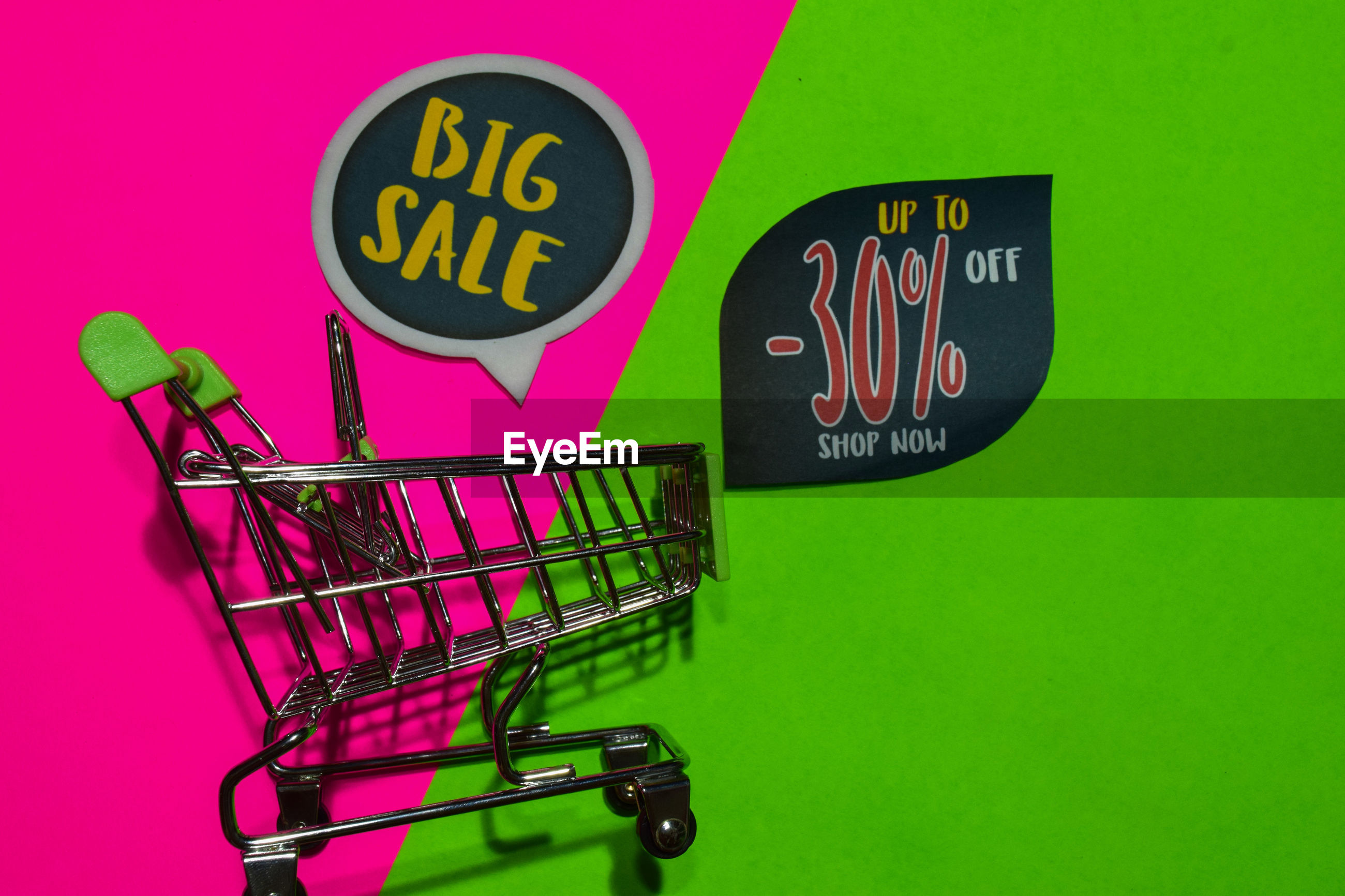 Close-up of shopping cart and labels on colored background
