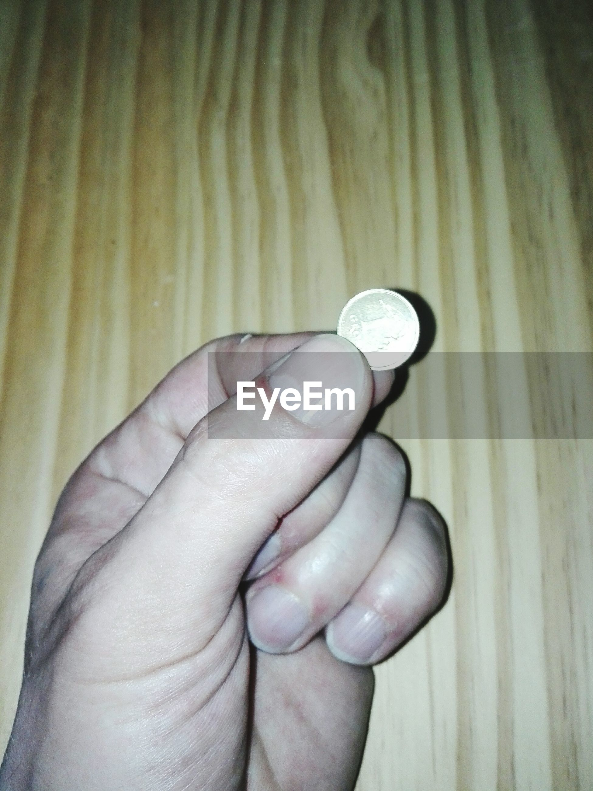Close-up of hand holding coin on table