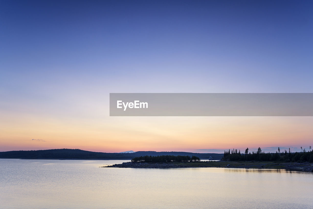 sky, sunset, water, scenics - nature, beauty in nature, tranquility, tranquil scene, waterfront, sea, copy space, no people, nature, orange color, idyllic, outdoors, silhouette, clear sky, architecture