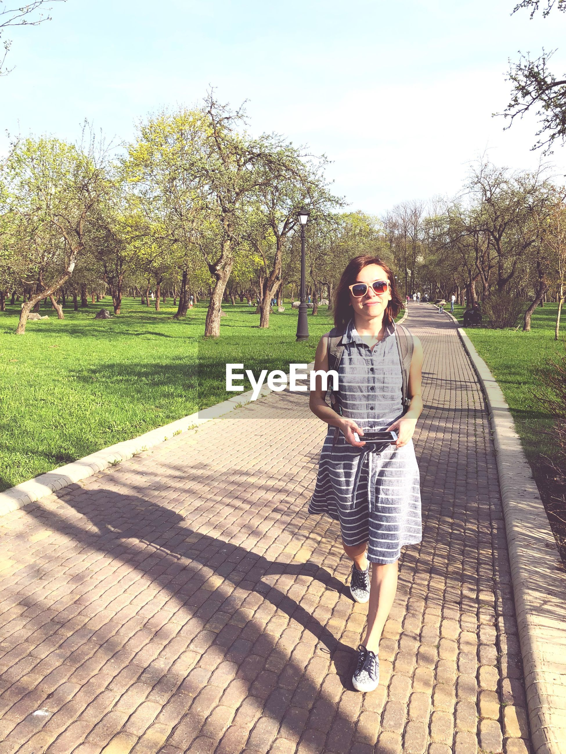 one person, full length, plant, tree, casual clothing, real people, nature, looking at camera, front view, leisure activity, day, lifestyles, footpath, portrait, shadow, sunlight, women, grass, standing, outdoors, beautiful woman