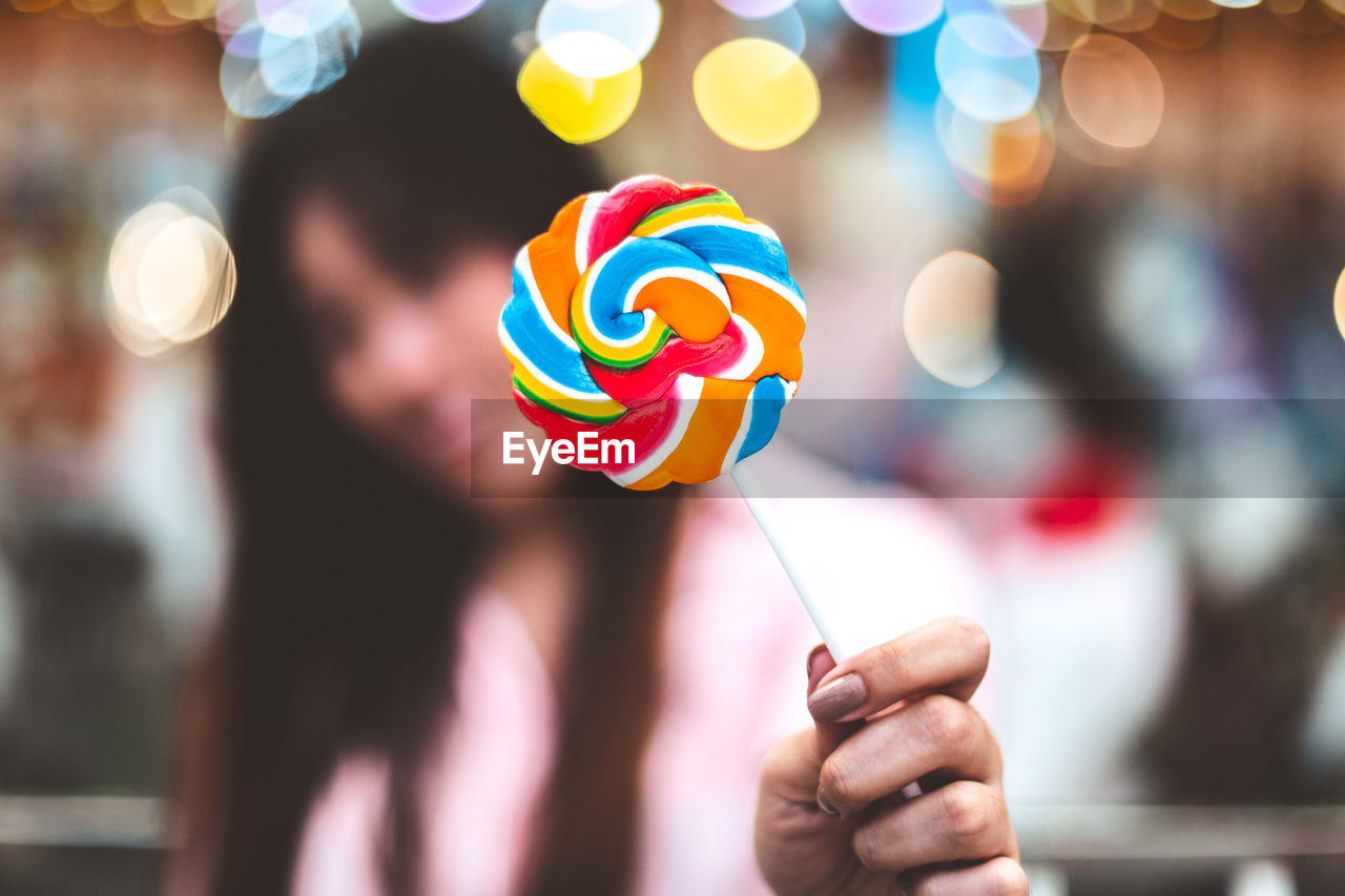 Close-up of woman holding colorful lollipop