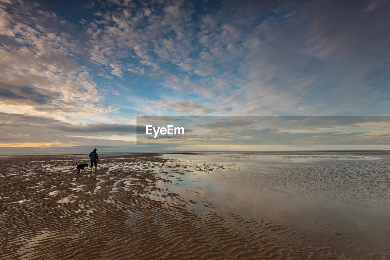 sky, water, sea, land, beauty in nature, beach, horizon over water, horizon, cloud - sky, real people, scenics - nature, tranquil scene, tranquility, sunset, nature, lifestyles, sand, one person, leisure activity