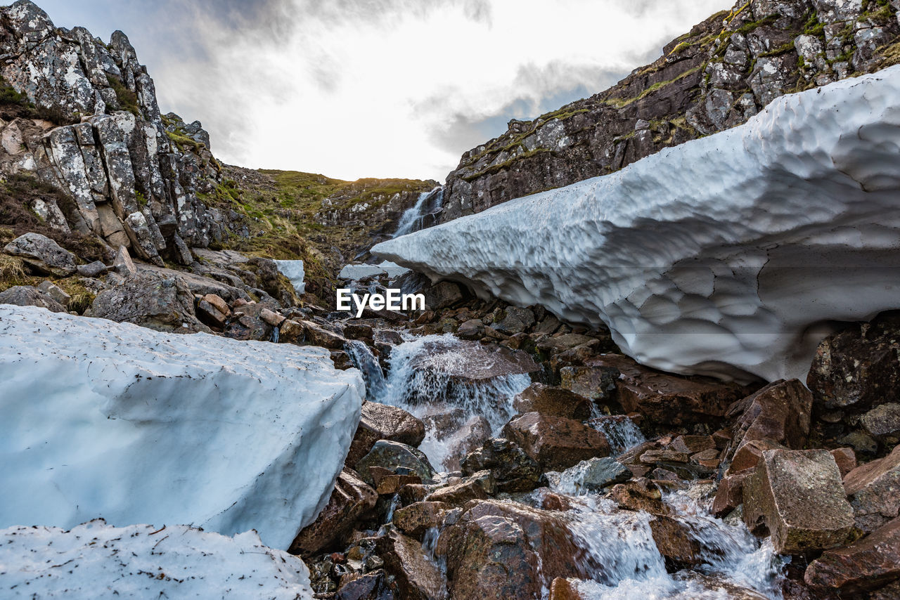 A mountain stream with residues of snow in the spring, ben nevis, fort william, scotland