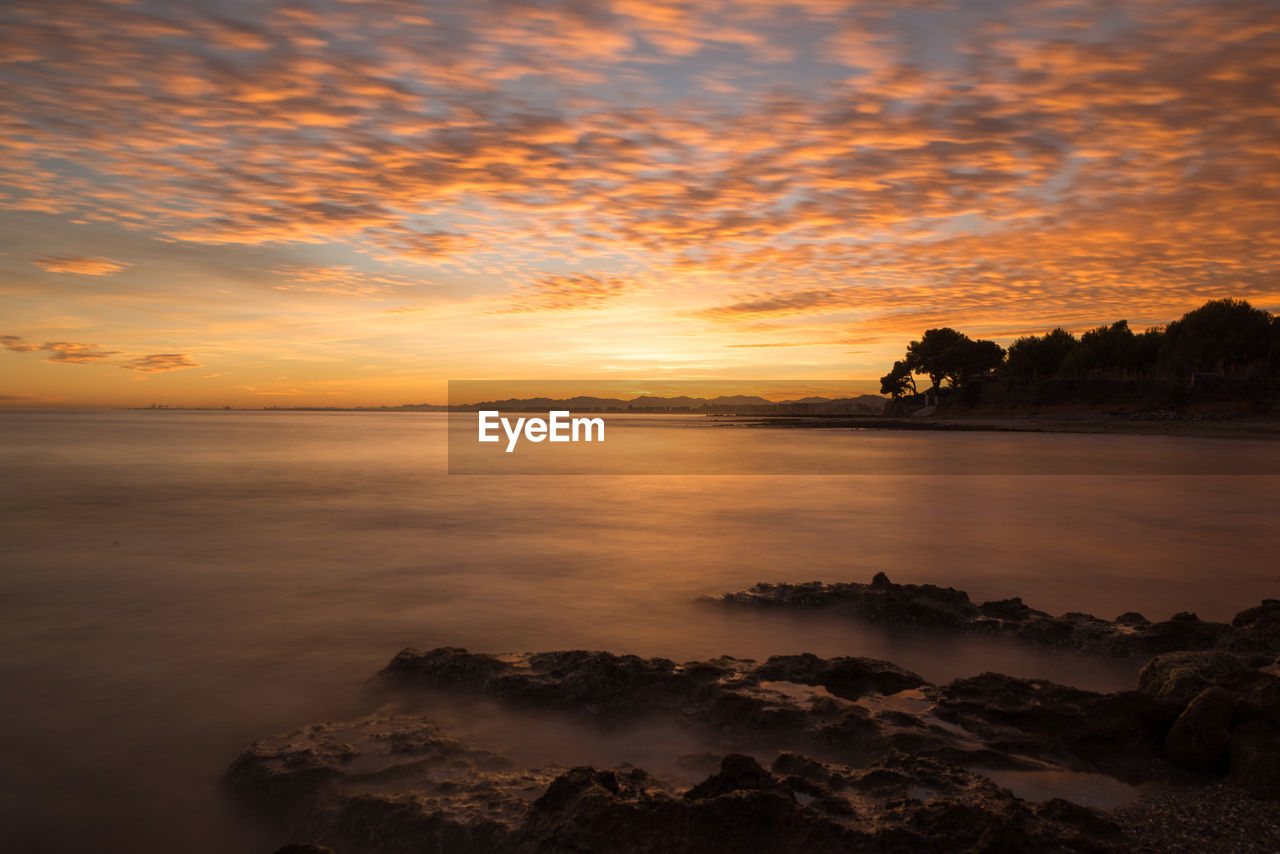 sunset, beauty in nature, sky, nature, scenics, orange color, tranquility, tranquil scene, water, sea, idyllic, cloud - sky, no people, silhouette, outdoors, landscape, tree