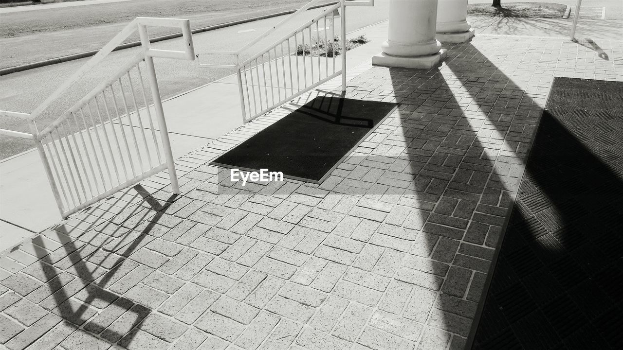 shadow, sunlight, footpath, railing, day, high angle view, street, nature, paving stone, outdoors, architecture, low section, real people, sidewalk, stone, city, cobblestone, lifestyles, focus on shadow