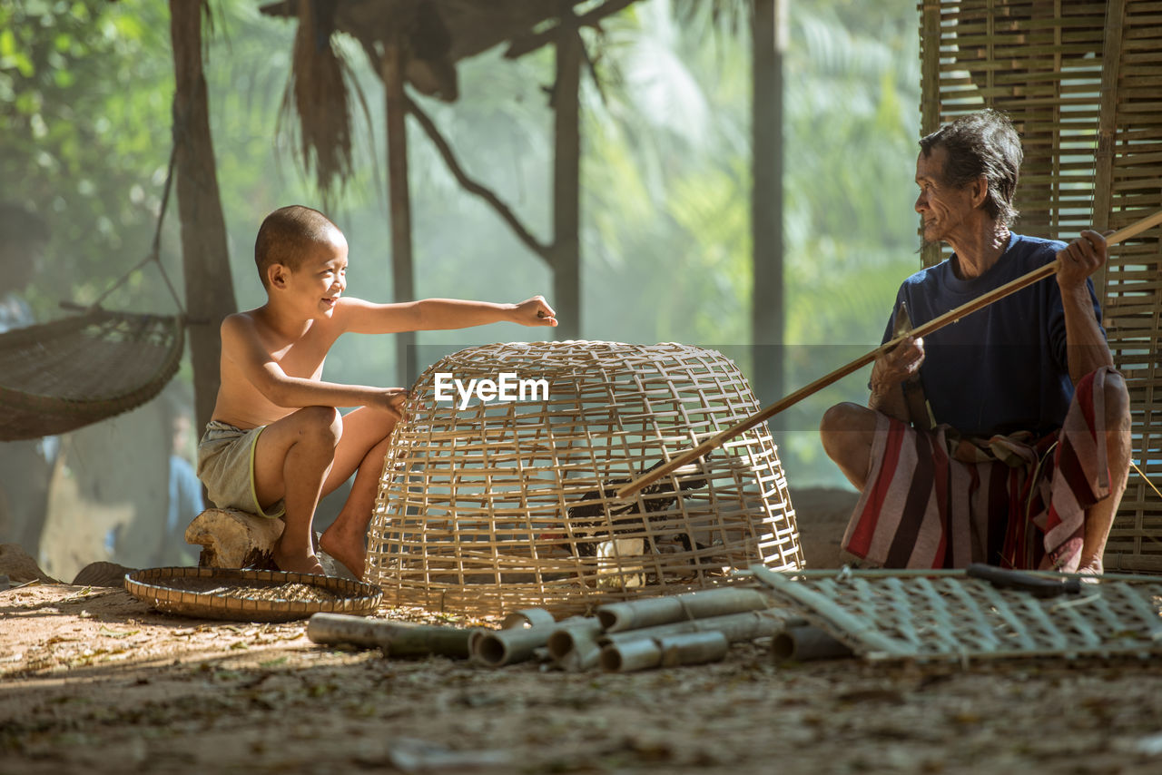 Boy and senior man removing chicken bird from wicker basket on field