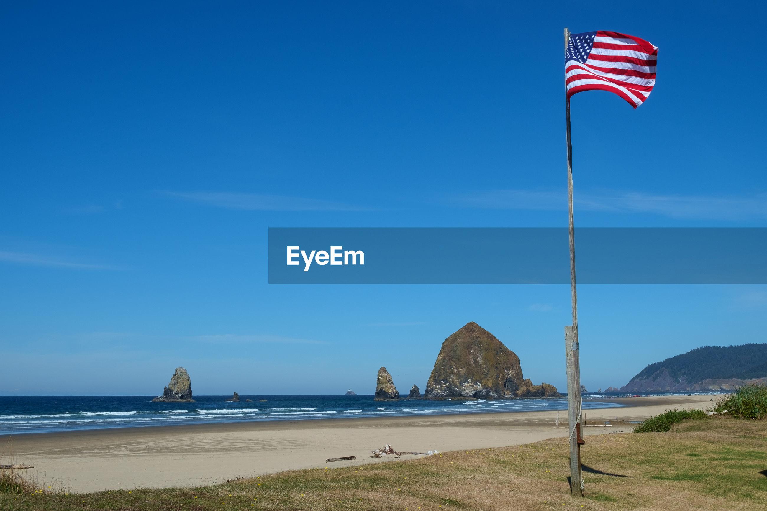 American flag on beach against blue sky