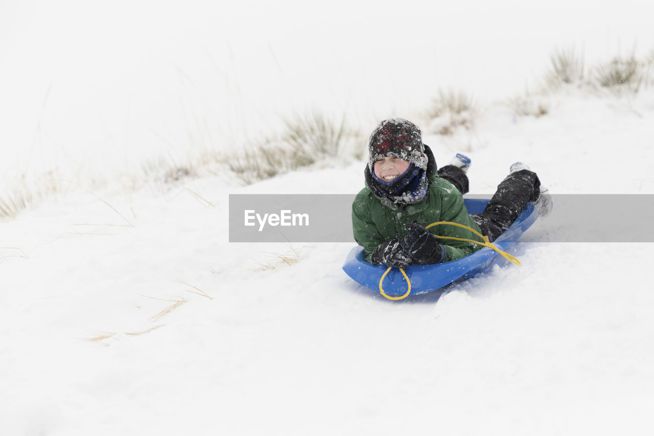 snow, winter, cold temperature, land, nature, warm clothing, childhood, field, day, child, white color, one person, clothing, leisure activity, real people, sled, boys, outdoors, playing, innocence, tobogganing