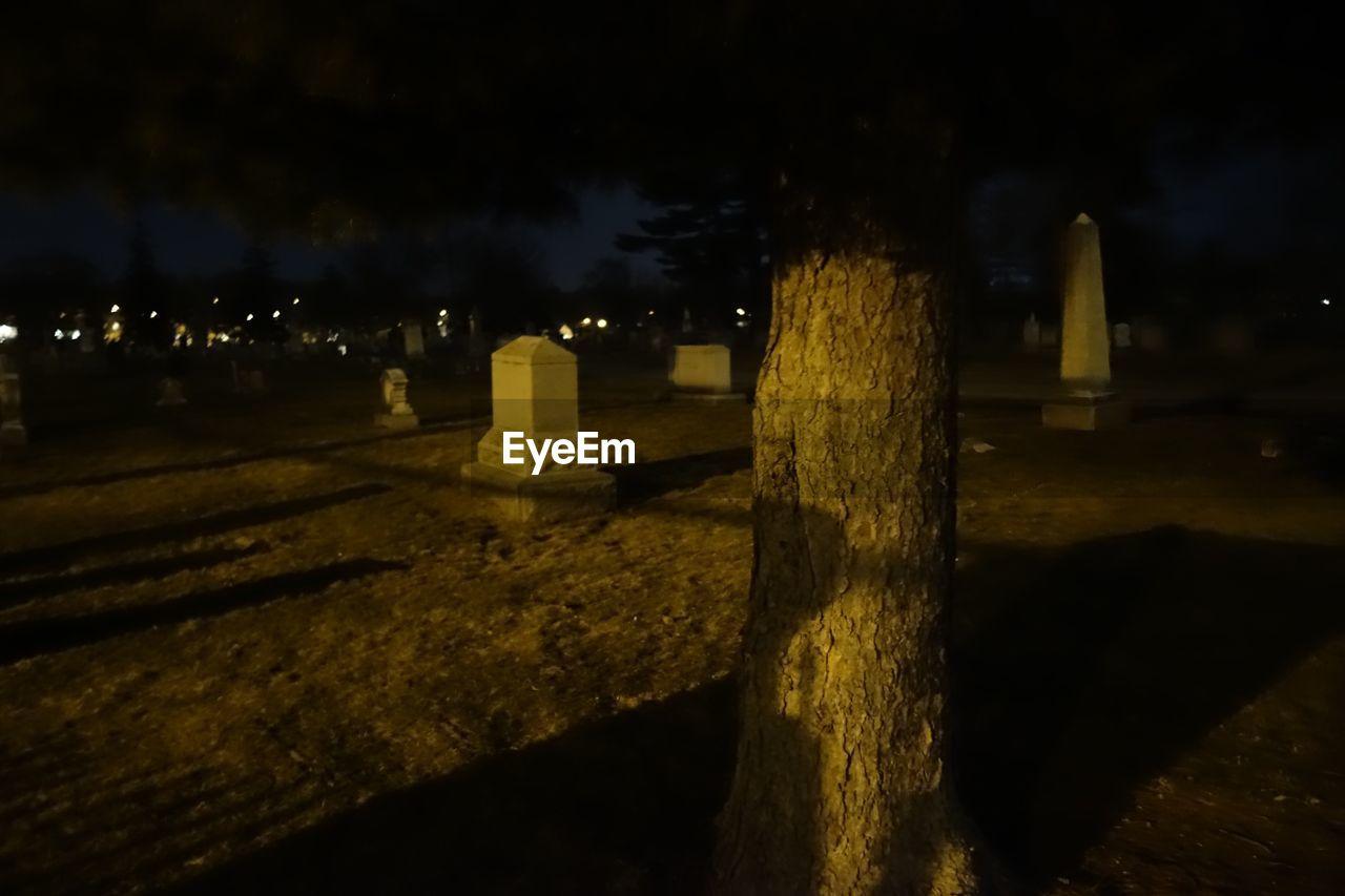 tombstone, cemetery, night, memorial, the past, graveyard, no people, gravestone, outdoors, illuminated, grave, cross, spirituality, nature, sky, tree, close-up