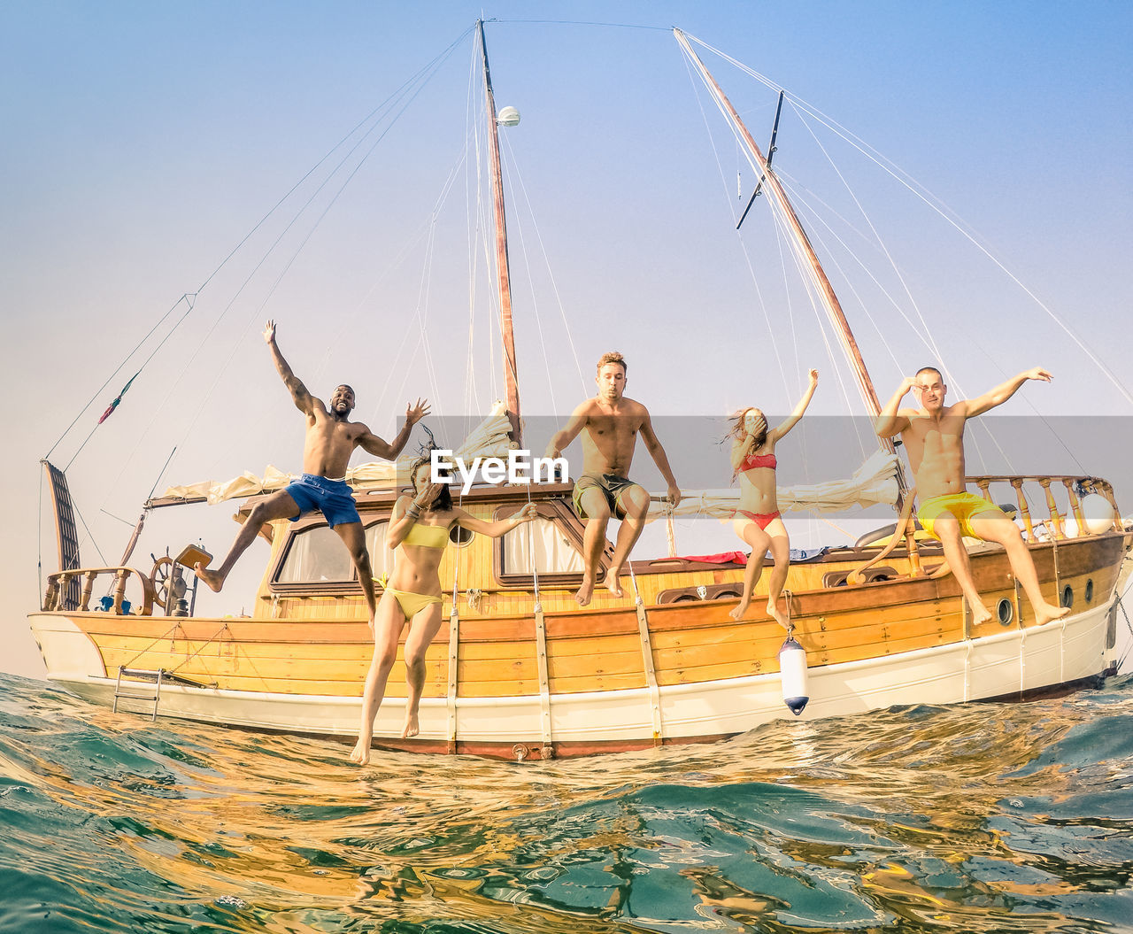 Low Angle View Of Friends Jumping From Boat In Sea
