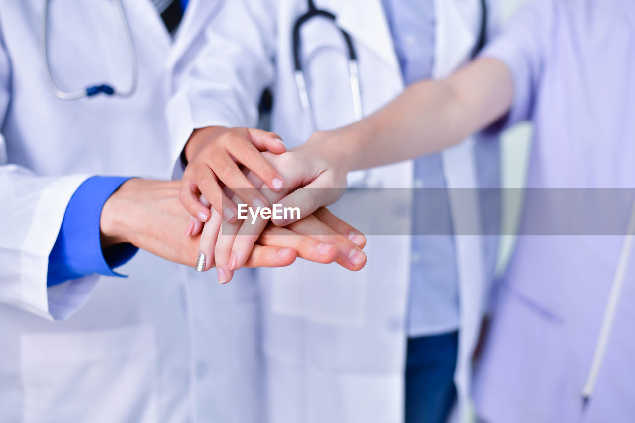 clothing, human hand, midsection, occupation, teamwork, cooperation, group of people, hand, adult, doctor, lab coat, real people, hospital, people, human body part, togetherness, men, indoors, healthcare and medicine, women, healthcare worker, care, responsibility, uniform, coworker