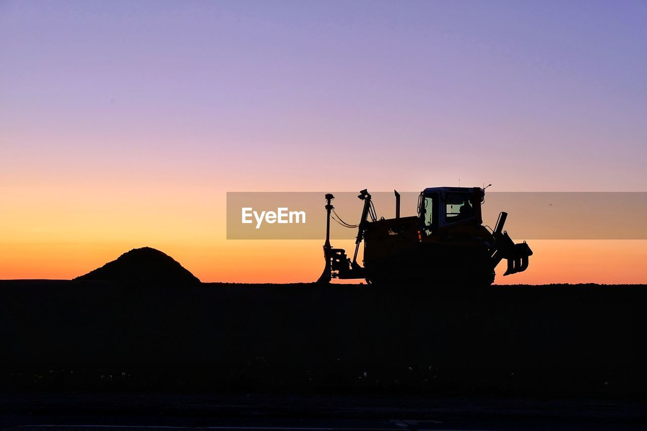 sky, sunset, silhouette, transportation, water, orange color, nature, beauty in nature, mode of transportation, machinery, industry, copy space, scenics - nature, land vehicle, men, clear sky, occupation, land, outdoors