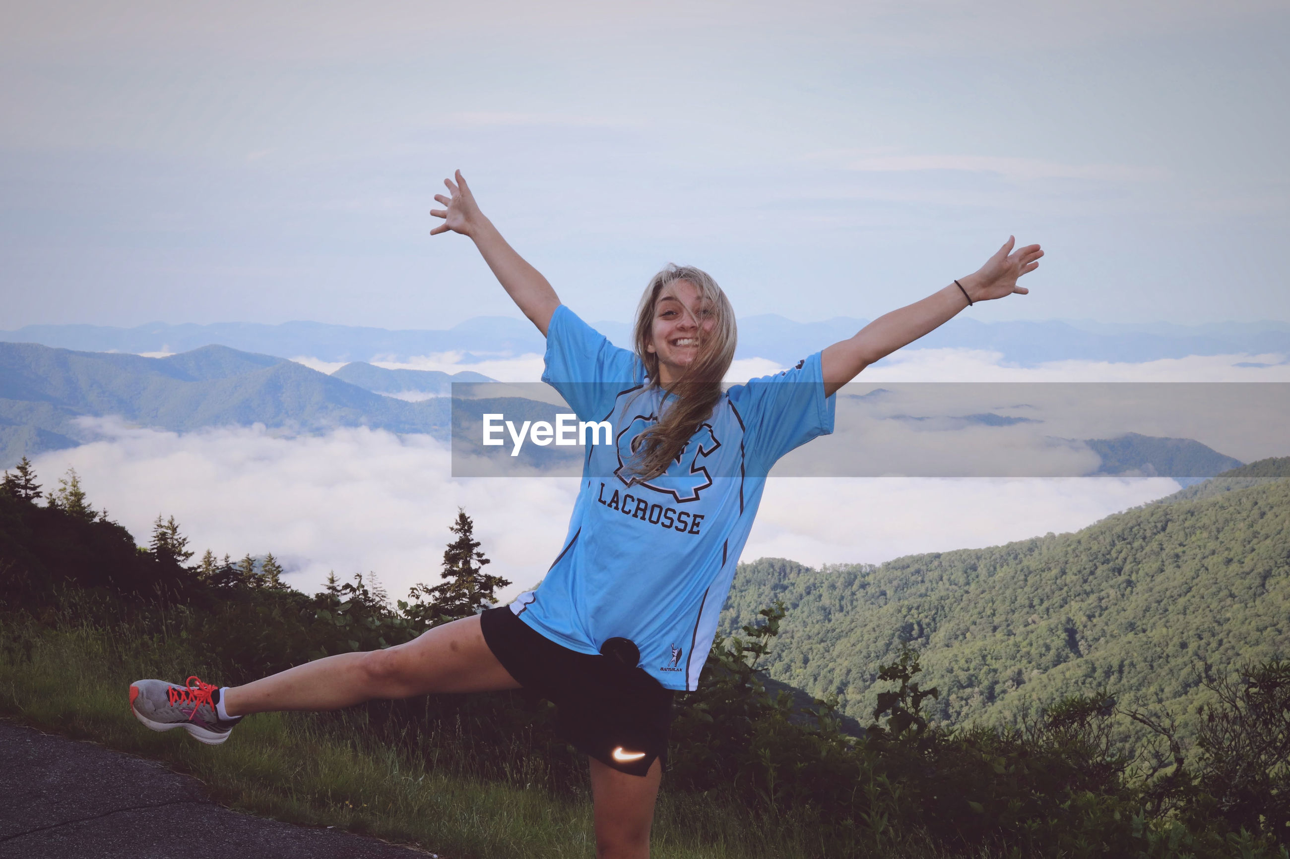 WOMAN WITH ARMS RAISED AGAINST MOUNTAIN RANGE