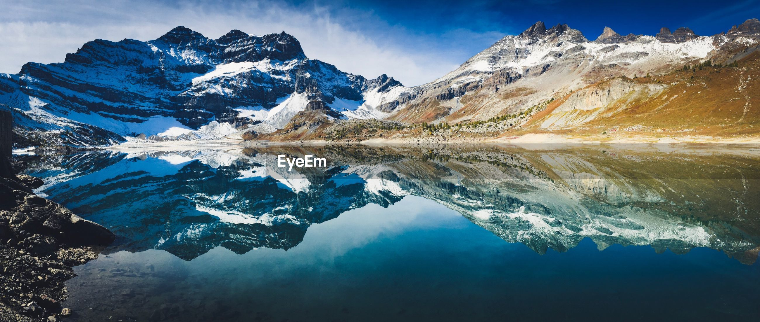 Panoramic view of snowcapped mountains reflection in lake