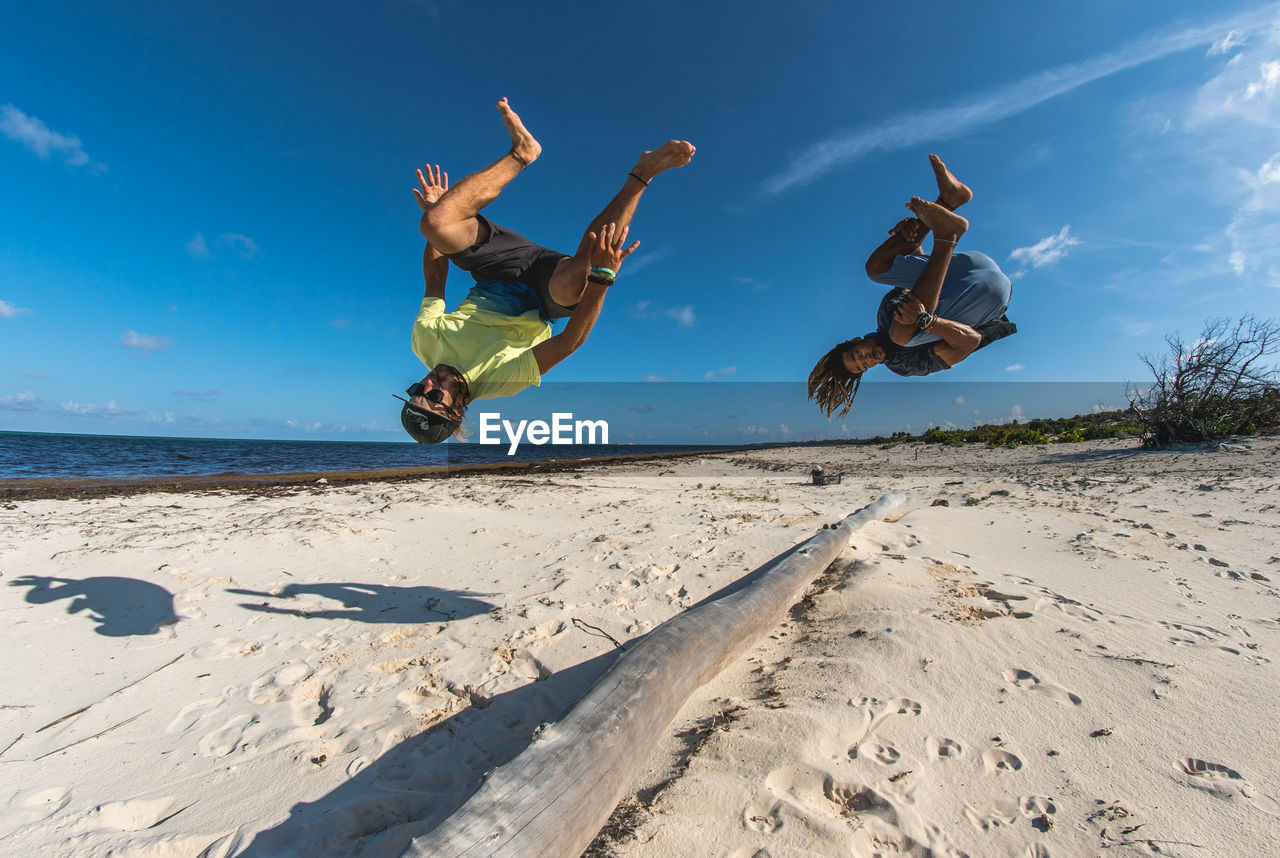 mid-air, sky, jumping, sand, real people, land, lifestyles, beach, nature, full length, leisure activity, enjoyment, fun, sunlight, day, motion, human arm, vitality, emotion, men, arms raised, positive emotion, outdoors, freedom