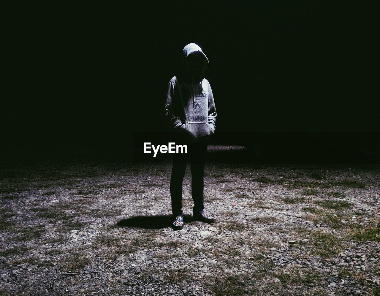 Man wearing hooded sweatshirt standing on illuminated ground