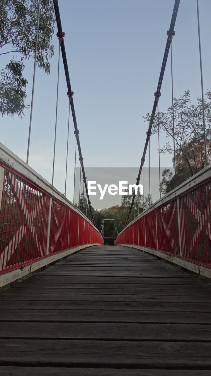 bridge - man made structure, connection, footbridge, railing, suspension bridge, day, outdoors, the way forward, bridge, sky, built structure, tree, low angle view, red, clear sky, architecture, no people, nature