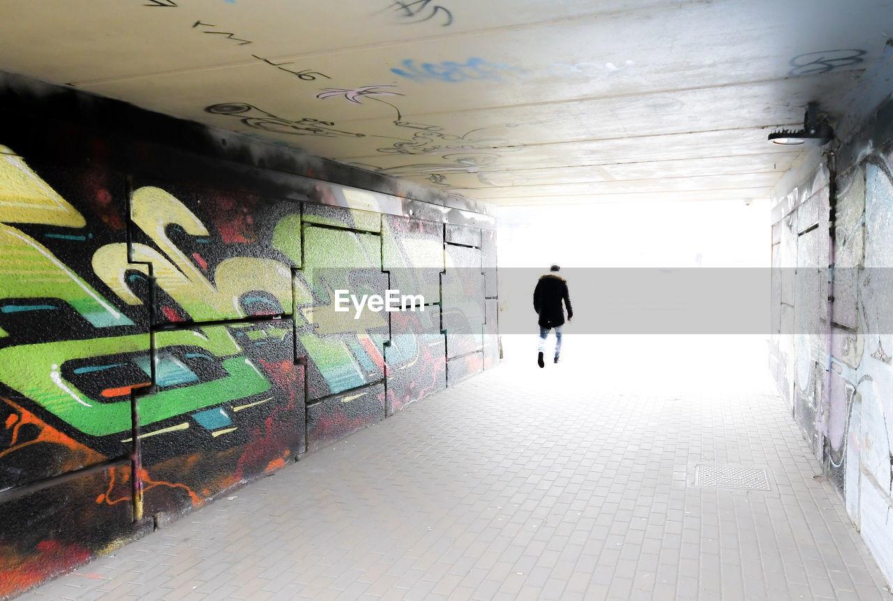 FULL LENGTH REAR VIEW OF MAN WALKING IN GRAFFITI