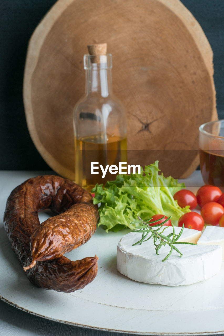 food and drink, food, vegetable, freshness, table, still life, ready-to-eat, healthy eating, indoors, no people, refreshment, tomato, drink, bottle, bread, container, cutting board, close-up, fruit, herb, french food
