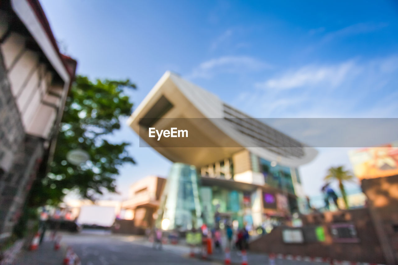 architecture, built structure, building exterior, sky, city, nature, building, day, incidental people, low angle view, outdoors, street, plant, focus on foreground, cloud - sky, selective focus, residential district, tree, transportation, car, consumerism
